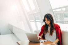 Calm And Peaceful Young Woman Working At Table Near Window. Type On Keyboard Of Laptop. Alone In Room. Wear Stylish Red Jacket. Productive Day.