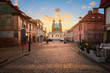 Leinwanddruck Bild - Historical road leading towards Gniezno Royal Cathedral on a sunset.