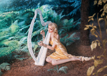 Fabulous Forest Elf Sits Under Tree And Plays On White Harp, Girl With Long Blond Hair Braided In Long Yellow Dress, Summer Goddess Rests And Sings To The Sound Of A Magical Musical Instrument.