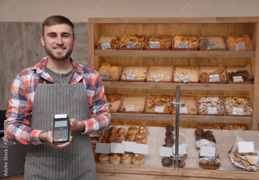 Fototapeta Smiling seller holding payment terminal in bakery. Space for text