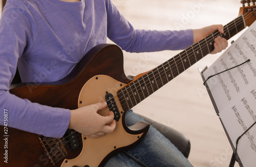 Child playing guitar at music lesson, closeup. Learning notes - 274750877
