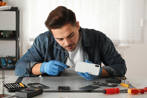Foto  Technician repairing broken smartphone at table in workshop