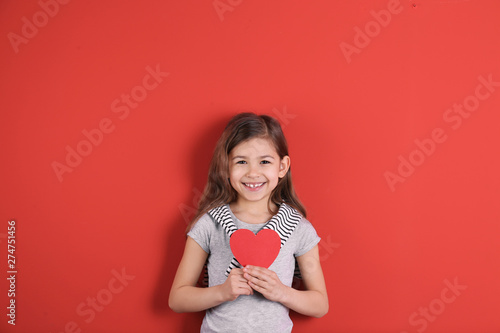 Portrait of girl with paper heart on color background