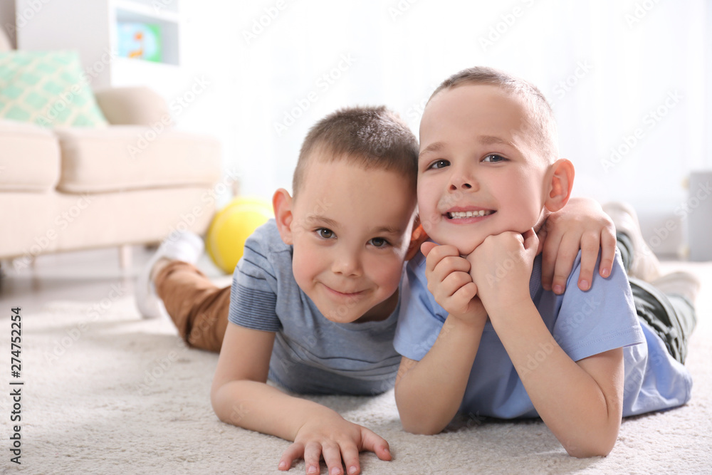 Fototapety, obrazy: Portrait of cute twin brothers on floor in living room