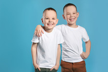 Portrait Of Cute Twin Brothers On Color Background