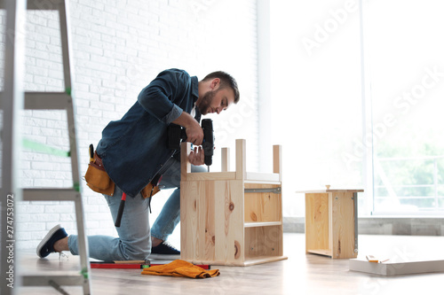 Fotografia Young man working with electric screwdriver indoors