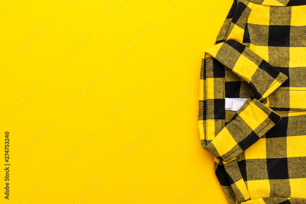 Fototapety, obrazy: yellow and black checkered shirt on the yellow background. top view of yellow shirt with copy space.
