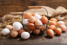 Basket Of Colorful Fresh Eggs On Wooden Table