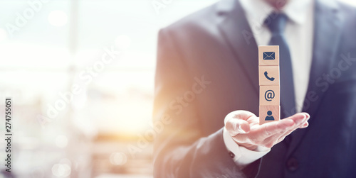 Fotomural  CONTACT US, Businessman holding three wooden blocks in his hand with icon telephone, mail and email, Online business communications concept, copy space