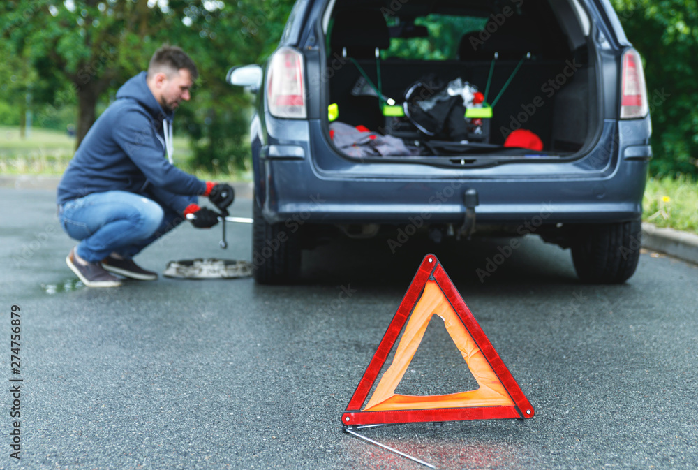 Fototapety, obrazy:  Warning triangle and man changing car wheel