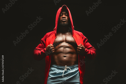 Fotomural  Confident african bodybuilder in red hooded shirt with bare chest
