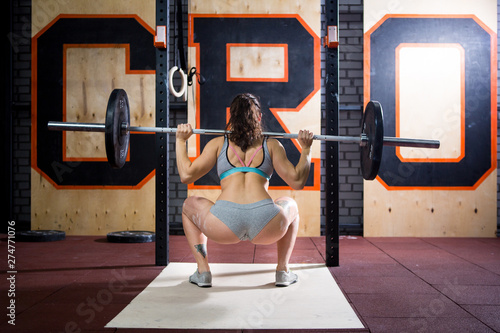 Sport and health theme. A beautiful sexy girl with a bare booty in a bikini stands tired near the bar and rests after a hard training session. Deadlift and training of leg and back muscles