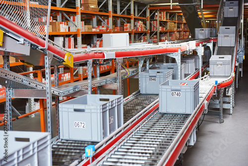 Fotografía Automated warehouse. Boxes with spare parts moving on conveyer
