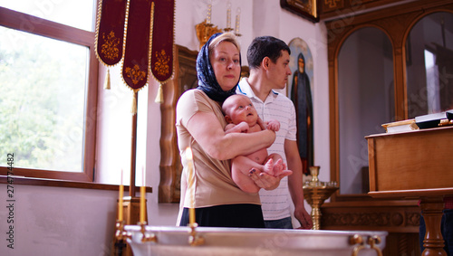 Valokuva  Rite of the baptism of the little boy in the Christian tradition