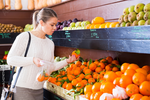 Poster Individuel Girl choosing fruits in grocery
