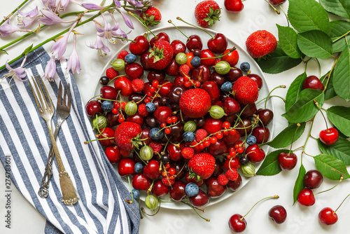 Poster Pays d Europe Various fresh summer berries in a plate with fork on white marble table. Top view. healthy diet food