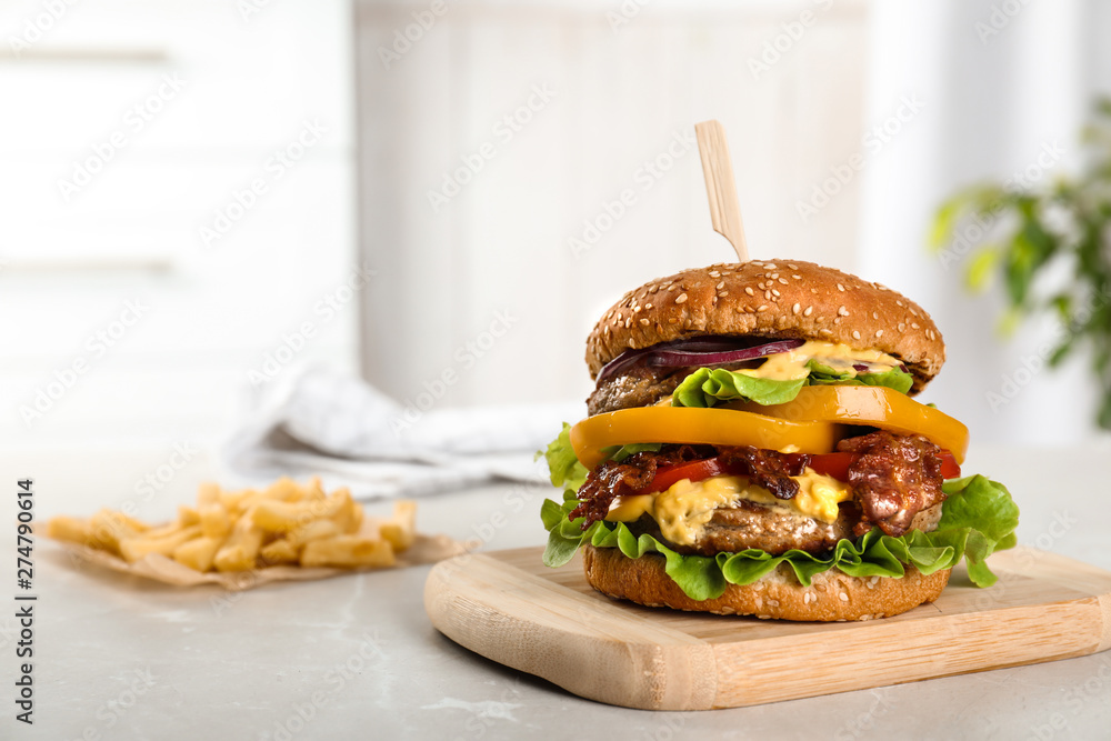 Fototapety, obrazy: Board with tasty burger on table. Space for text