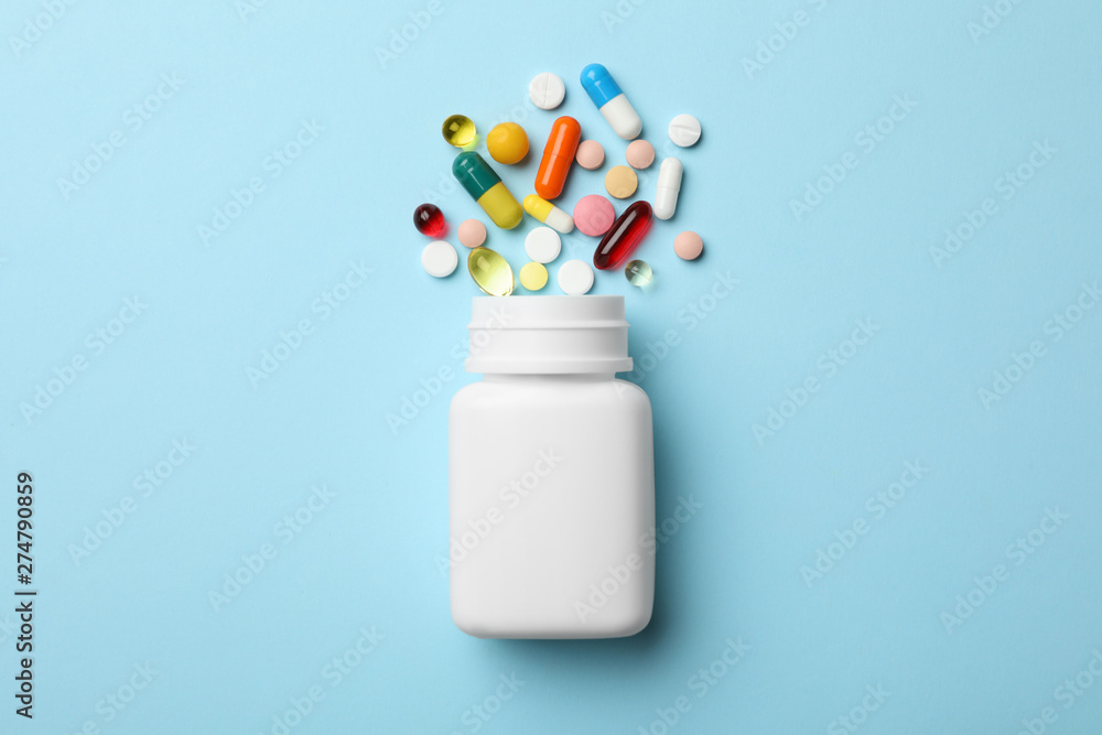 Fototapeta Bottle and scattered pills on color background, top view