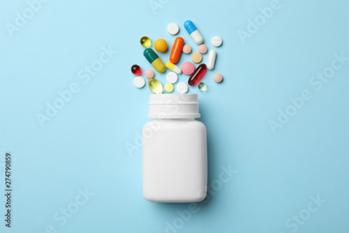 Bottle and scattered pills on color background, top view Fototapeta