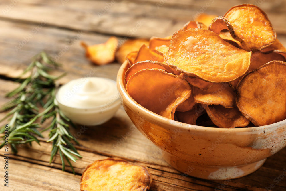 Fototapeta Delicious sweet potato chips in bowl, rosemary and sauce on table. Space for text