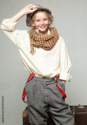 teen girl in retro male suit. retro fashion model. Vintage suspender. old fashioned child in beret. street kid with dirty face. vintage english style. Travel with old suitcase. Homelss. traveling