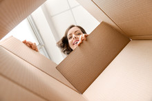 Young Woman Opening Parcel At Home, View From Inside Of Box