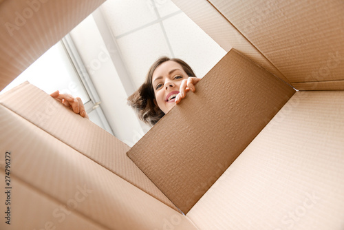 Obraz Young woman opening parcel at home, view from inside of box - fototapety do salonu