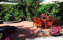 Beautiful And Lush Summertime Mediterranean Style Courtyard Garden With Wooden Table And Chairs And White Market Umbrella.