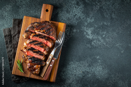 Fotografiet Sliced steak ribeye, grilled with pepper, garlic, salt and thyme served on a wooden cutting Board on a dark stone background