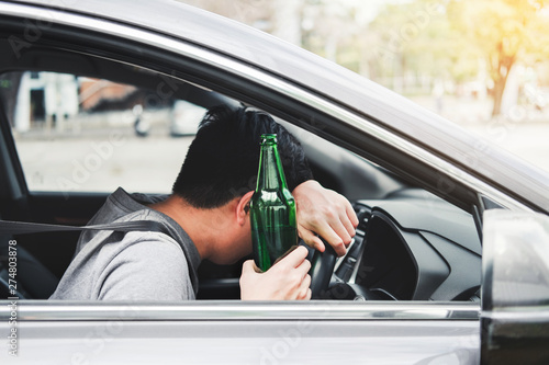 Photo  Drunk man driving a car on the road holding bottle beer Dangerous drunk driving