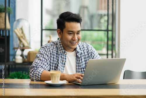 Foto  Smart Asian man working with laptop in cafe, work concept and copy space