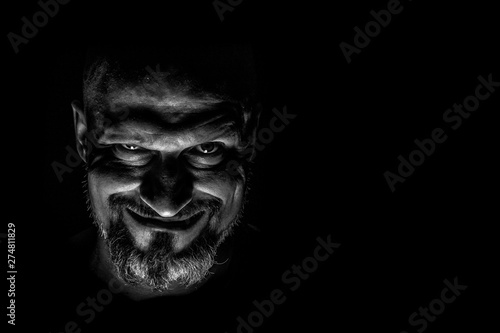 Fotografie, Tablou Face with a bearded man grimace against a dark background with sharp shadows