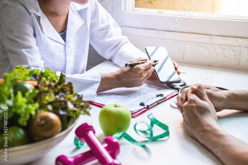 Fotomural Nutritionist giving consultation to patient with healthy fruit and vegetable, Ri