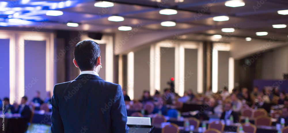 Fototapeta Speaker giving a talk at a corporate business conference. Audience in hall with presenter in front of presentation screen. Corporate executive giving speech during business and entrepreneur seminar.