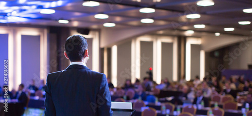 Obraz Speaker giving a talk at a corporate business conference. Audience in hall with presenter in front of presentation screen. Corporate executive giving speech during business and entrepreneur seminar. - fototapety do salonu