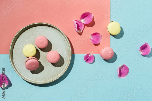 Foto auf Gartenposter Macarons Pastel flatlay of yellow and pink vegan macaroons with rose petals