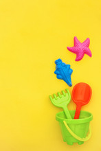 Multicolored Set Children's Toys For Summer Games In Sandbox Or On Sandy Beach On Yellow Background With Copy Space. Top View Flat Lay Concept. Template For Your Text Or Design