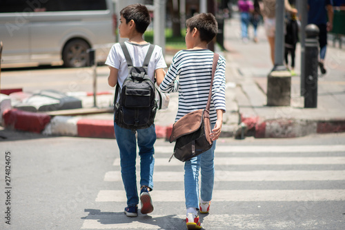 Little brother boys cross the road on the crosswalk Fotobehang