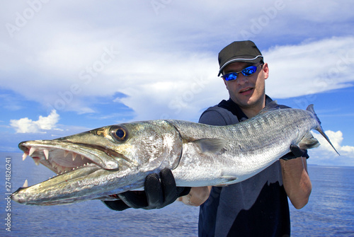 Poster de jardin Peche Deep sea fishing, catch of fish, big game fishing, fisherman holding a giant barracuda