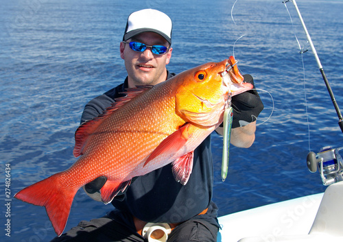 Stickers pour portes Peche fisherman holding a big red snapper fish, deep sea fishing, lure fishing, big game fishing. Catch of fish
