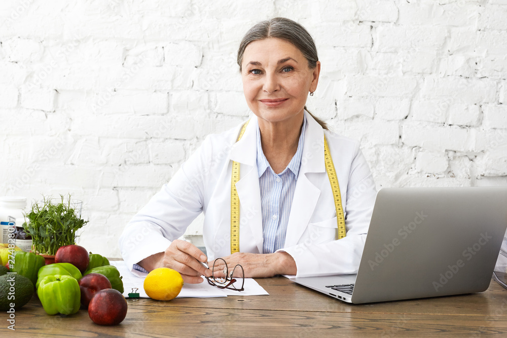 Fototapety, obrazy: Indoor shot of positive smiling Caucasian female nutritionist in her sixties working online, sitting in front of open laptop pc, consulting clients on nutrition via social networks, making notes