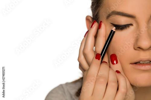 Fotografia Young woman applying eyelinear on white background
