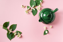Jasmine Tea With Teapot, Flowers And Leaves On Pink Background