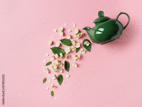 Photo Jasmine tea with teapot, flowers and leaves on pink background
