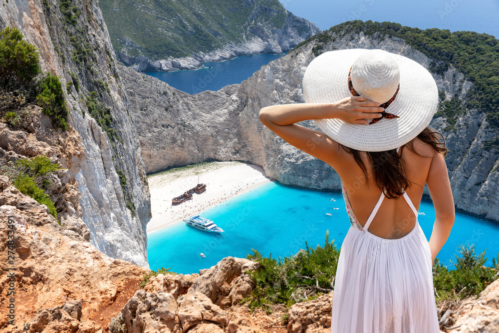 Fototapety, obrazy: Touristin in weißem Sommerkleid steht auf einer Klippe und genießt die Aussicht auf den berühmten Schiffswrack Strand, Navagio, auf der Insel Zakynthos, Griechenland