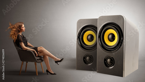 Stylish young lady sitting in a sofa and listening to big loudspeakers  - 274836699
