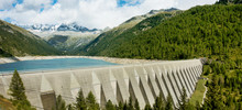 Big Concrete Dam With Scenery Of Lake, Forest And High Mountains.