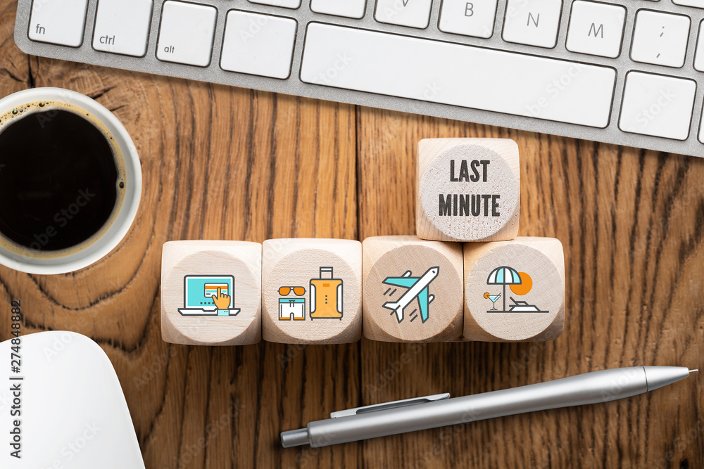 Fototapety, obrazy: Last minute online travel specials concept with a row of wooden blocks with icons depicting laptop, luggage, airplane and beach alongside a computer with mug of coffee