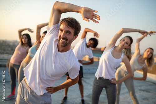 Group of fit healthy friends, people exercising together outdoor on rooftop - 274851021