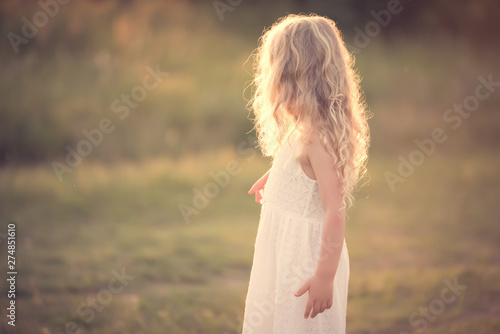 Fotomural  Beautiful blond little girl in the field